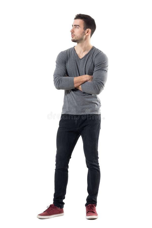 Hübscher junger zufälliger Mann mit den gekreuzten Händen, die weg schauen stockbild
