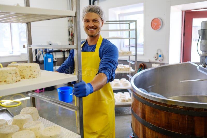 Hübscher Käsehersteller, der Quark in seiner Fabrik macht stockbilder