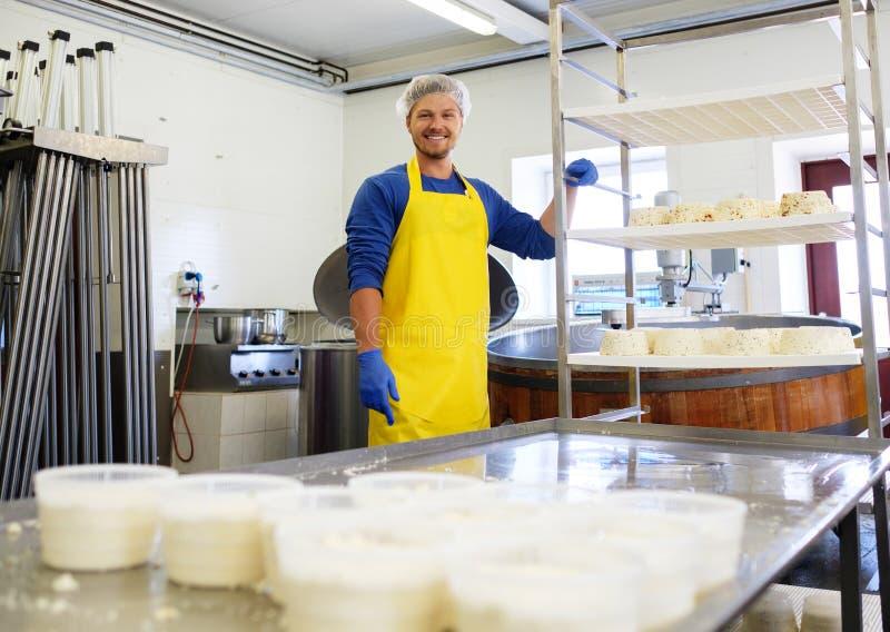 Hübscher Käsehersteller, der Quark in seiner Fabrik macht stockbild
