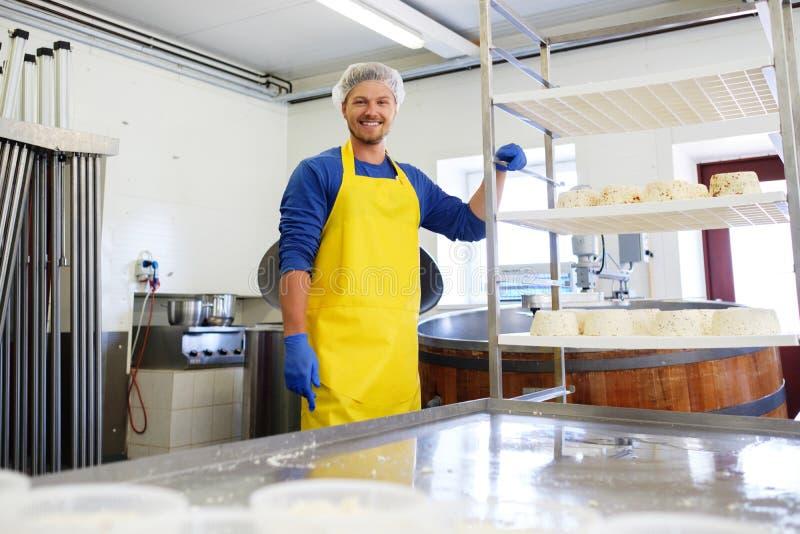 Hübscher Käsehersteller, der Quark in seiner Fabrik macht stockfotos