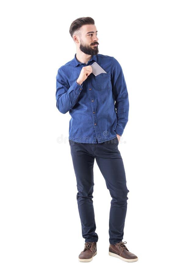 Hübscher kühler entspannter bärtiger Kerl setzte Mobiltelefon in die Hemdtasche ein, die weg schaut stockbilder