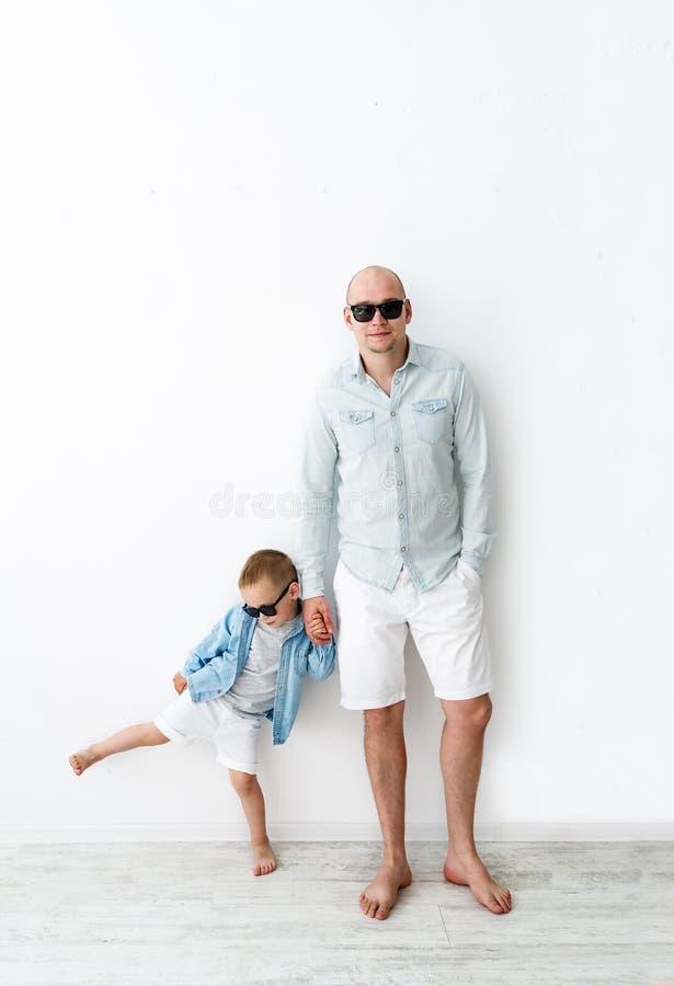 Hübscher kahler Mann in den schwarzen Gläsern mit seinem kleinen Sohn auf weißem Hintergrund stockfoto