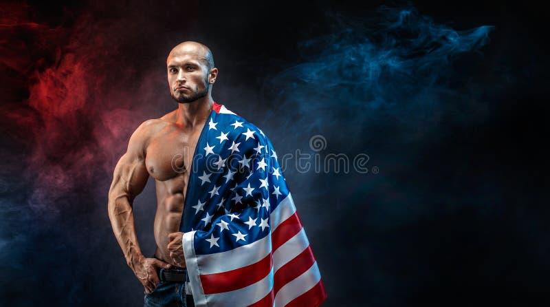 Hübscher kahler schulterfreier Mann mit amerikanischer Flagge auf Schulter stockbild