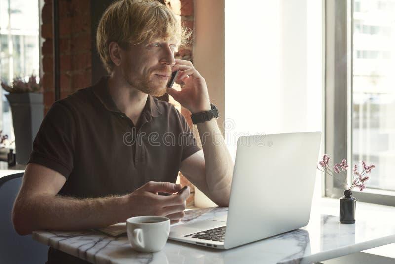 Hübscher kaukasischer Mann, der telefonisch unter Verwendung des Laptops beim Sitzen im Café hat Kaffeepause spricht lizenzfreie stockbilder