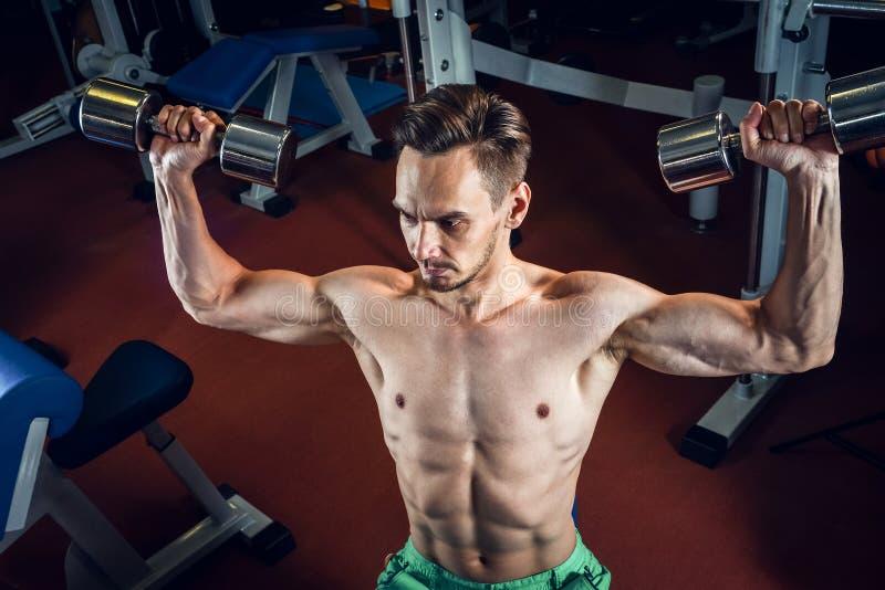 Hübscher kaukasischer Mann, der an der Turnhalle ausarbeitet und Schulterübungen mit dumbells tut stockbilder