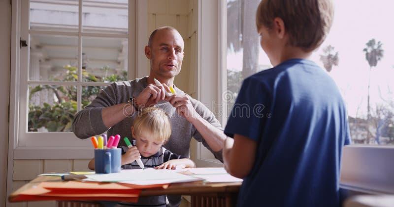 Hübscher kaukasischer Vater, der mit seinen zwei Jungen kritzelt stockfoto