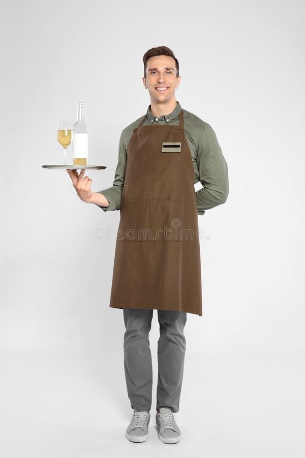 Hübscher Kellner, der Behälter mit Glas und Flasche hält lizenzfreie stockfotos