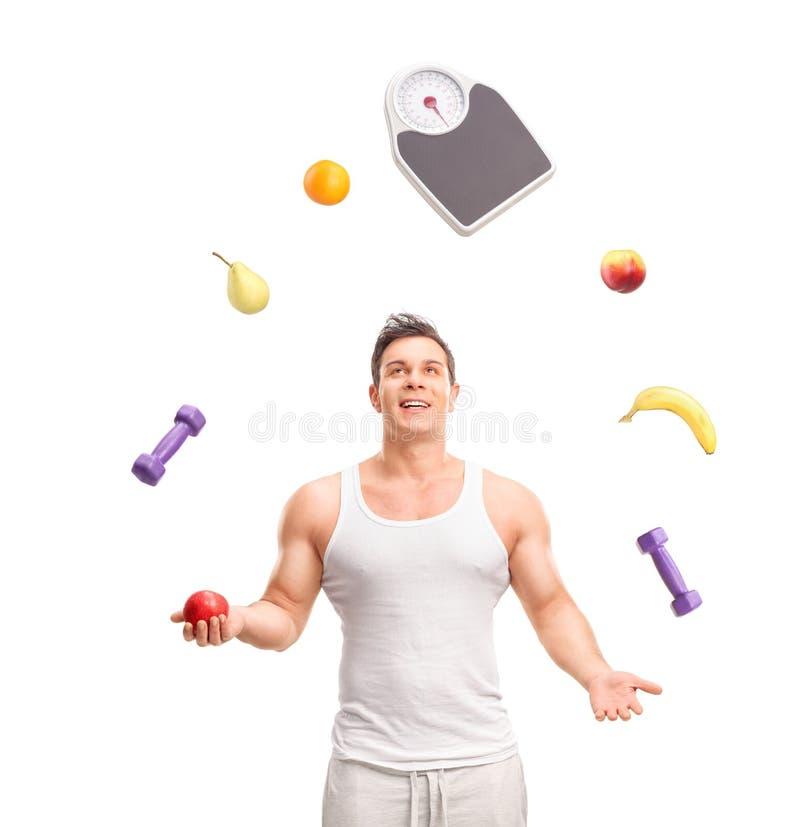 Hübscher Kerl, der mit Früchten jongliert stockfotos