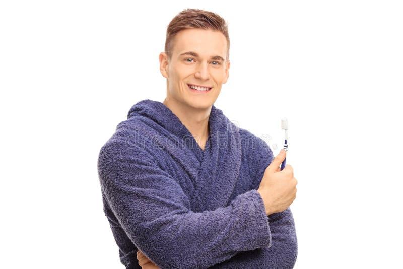 Hübscher Kerl in einem Bademantel, der eine Zahnbürste hält stockbild