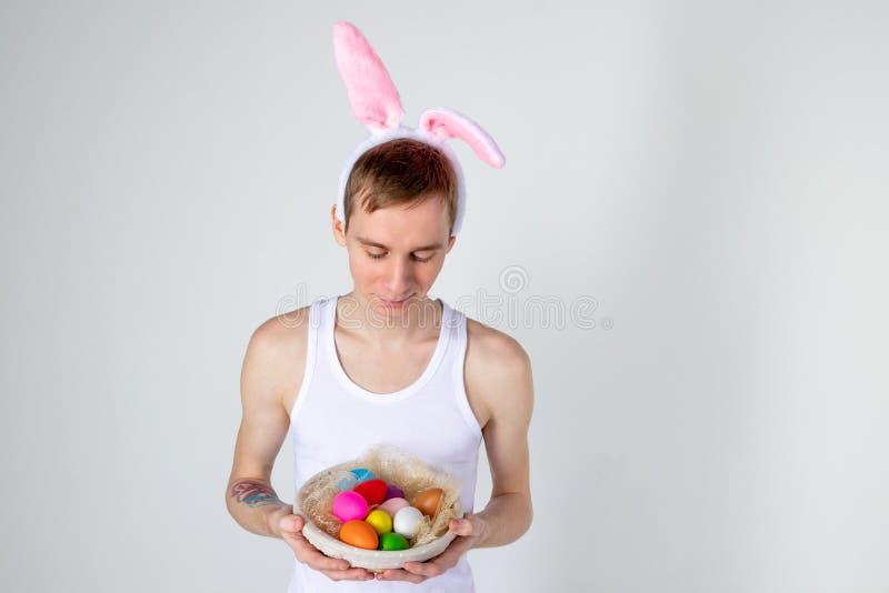 Hübscher Kerl mit den Häschenohren, die Korb mit Eiern halten Glückliches Ostern-Konzept stockbild