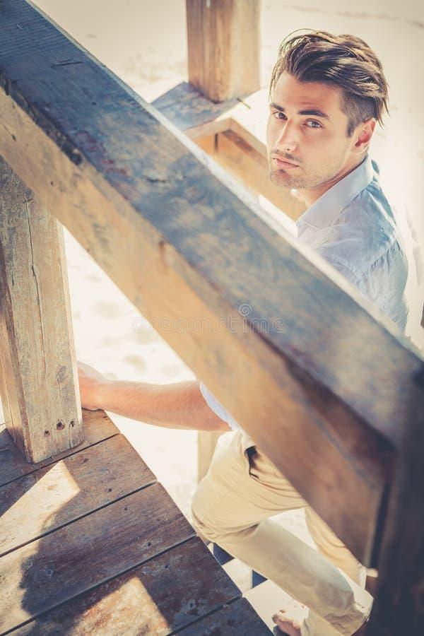 Hübscher Kerl mit der modischen Frisur, die hölzerne Treppe beim Schauen hinuntergeht stockfotografie