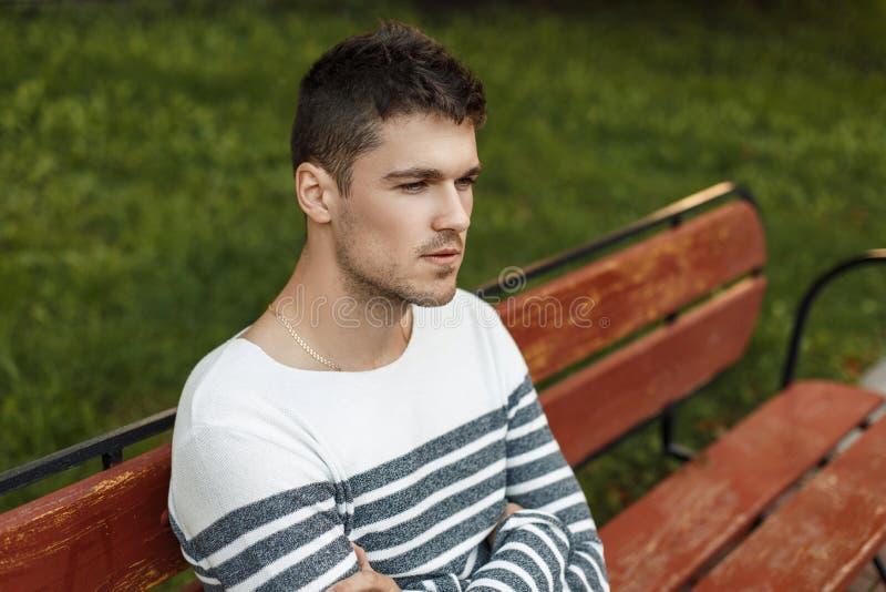 Hübscher Kerl mit einem Bart in einem stilvollen Pullover sitzt lizenzfreies stockbild