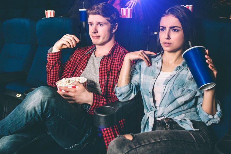 Hübscher Kerl und schönes Mädchen sitzen zusammen und aufpassender Film Ihre rechten Hände werfen auf Mädchen hält a lizenzfreies stockbild