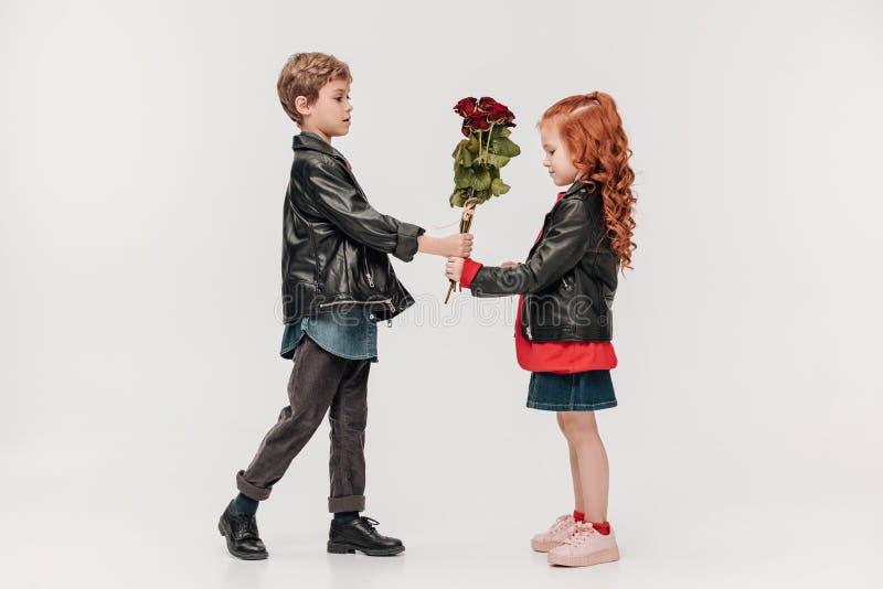 hübscher kleiner Junge, der Rosen Blumenstrauß seiner Freundin darstellt stockfotografie
