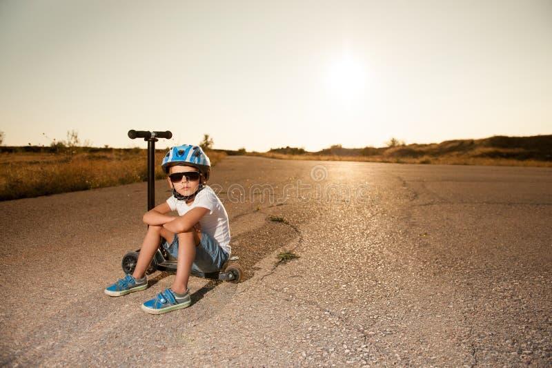 Hübscher kleiner Junge in der Sonnenbrille und Sturzhelm, der auf Roller auf verlassener Straße sitzt stockfotografie