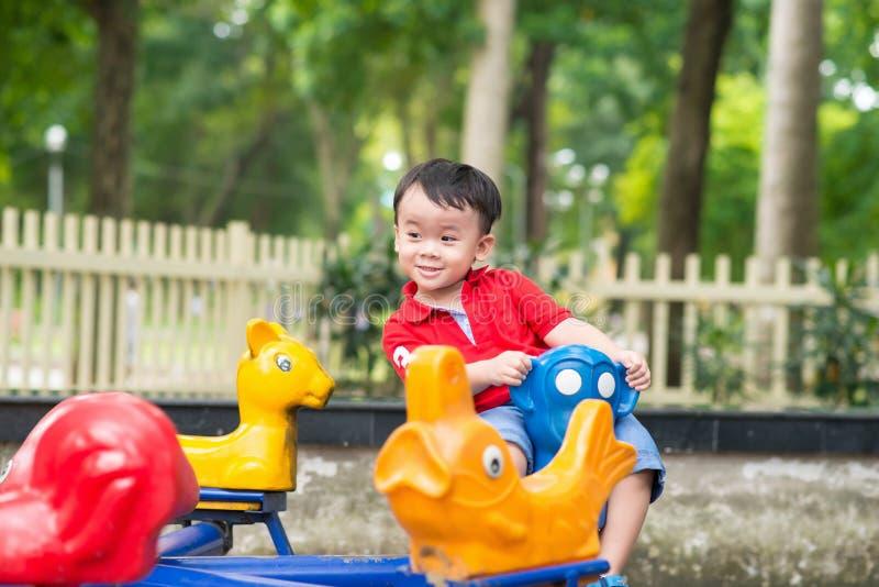 Hübscher kleiner Junge im Hemd spielt auf kleinem Karussell stockfoto