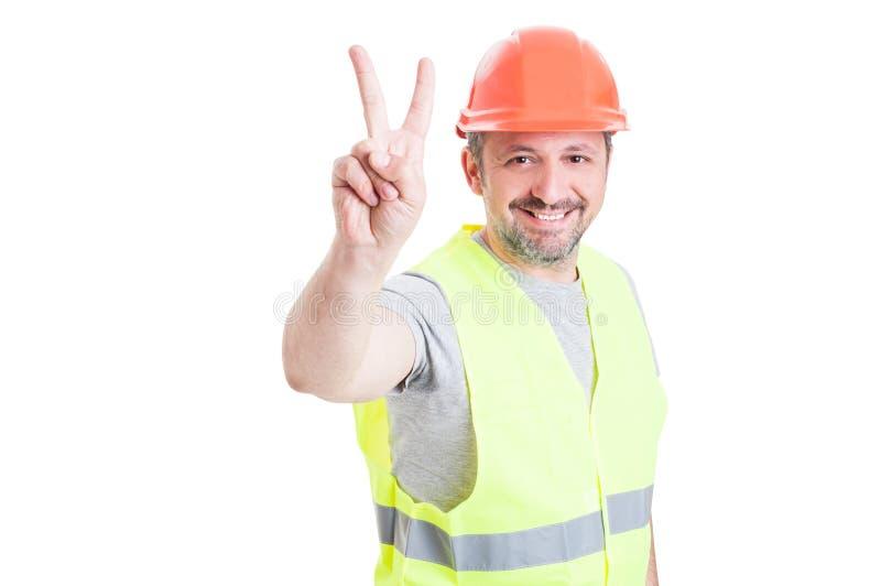 Hübscher lächelnder Arbeiter oder Erbauer mit dem Sturzhelm, der vict zeigt lizenzfreies stockbild