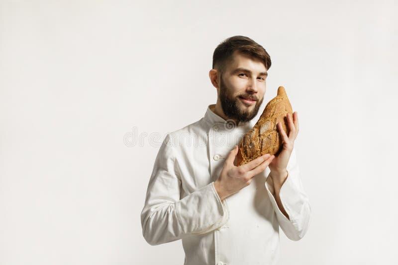 Hübscher lächelnder BÄCKER, der ein frisch gebackenes Laib im kitc riecht stockfotografie
