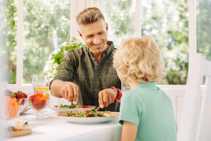 Hübscher lächelnder Ehemann beim Schnitt des Salats für seinen gelockten Sohn stockfotografie