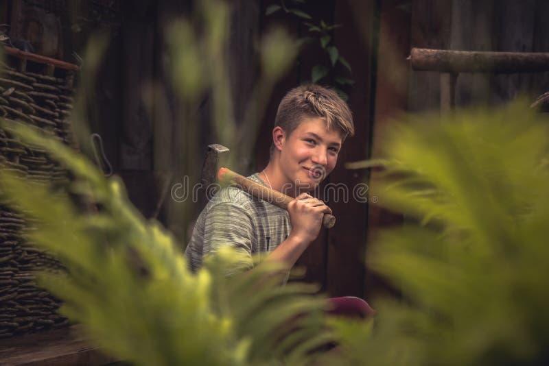 Hübscher lächelnder Jugendlichjunge mit Hammer auf seiner Schulter am Freienschmied unter Blättern während Landschaftssommerlager stockfotos
