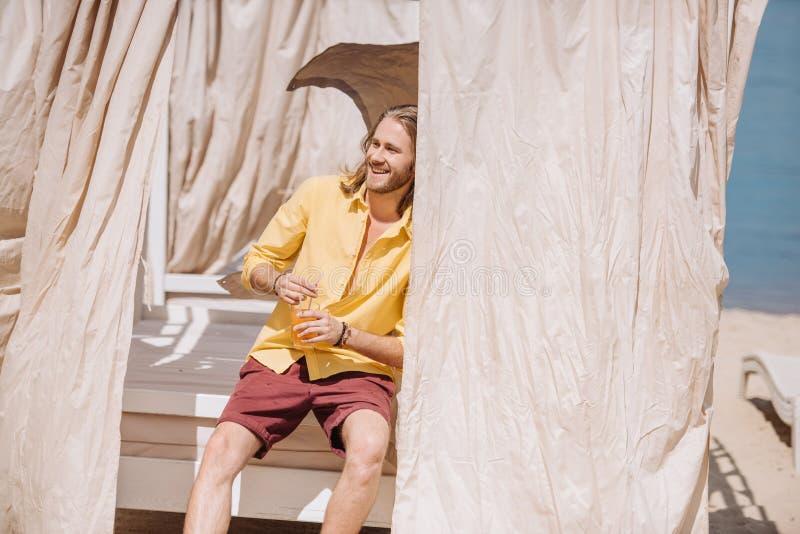 hübscher lächelnder junger Mann, der Glas des Cocktails beim Sitzen im Bungalow hält lizenzfreie stockbilder
