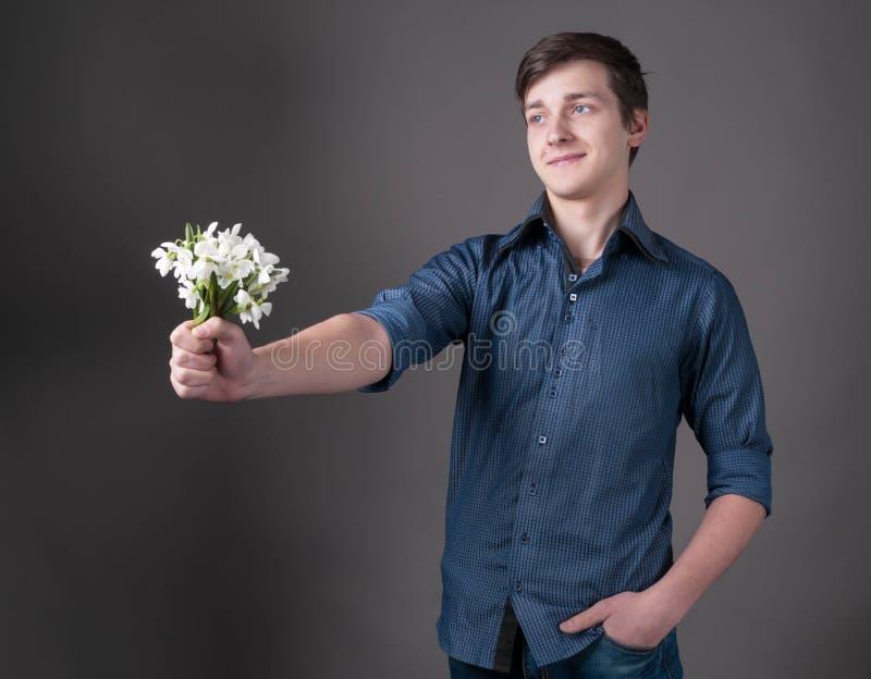Hübscher lächelnder junger Mann im blauen Hemd, das in ausgestrecktem Handblumenstrauß mit weißen Schneeglöckchen hält lizenzfreie stockfotografie