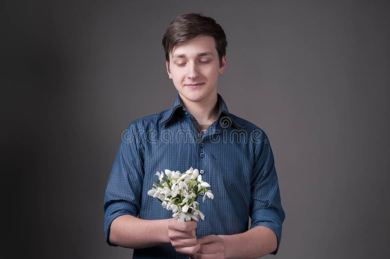 Hübscher lächelnder junger Mann im blauen Hemd, das Blumenstrauß von Schneeglöckchen hält und betrachtet stockbilder