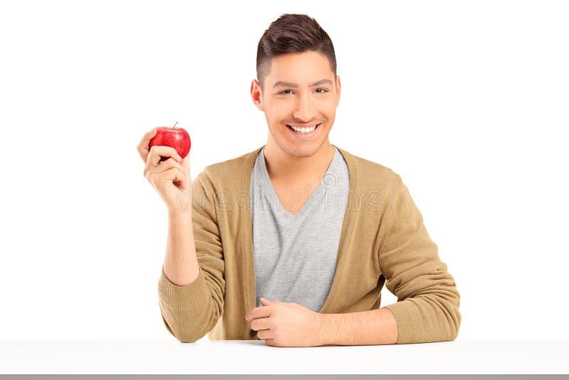 Hübscher lächelnder Kerl, der einen roten Apfel anhält und auf einer Tabelle aufwirft lizenzfreie stockbilder