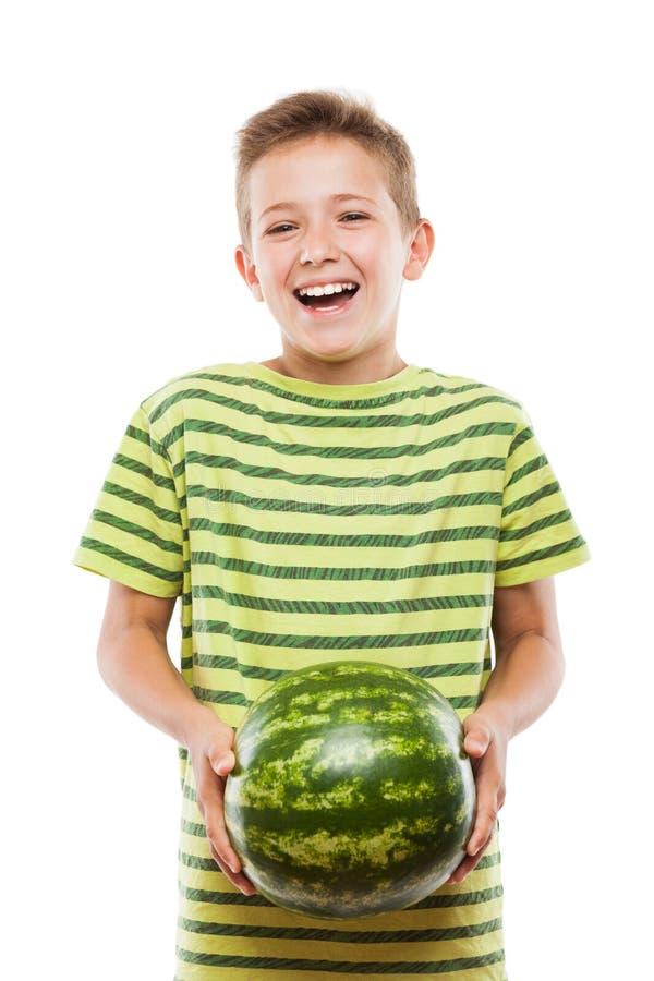 Hübscher lächelnder Kinderjunge, der grüne Wassermelonenfrucht hält stockfotografie