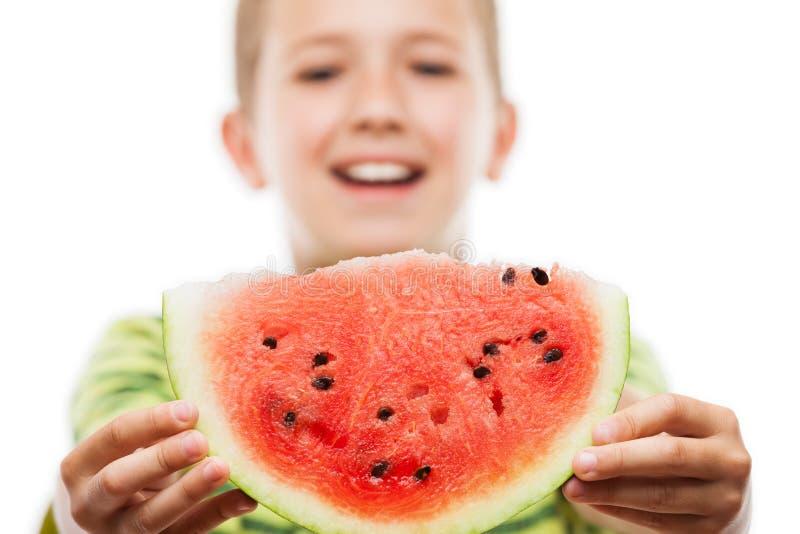 Hübscher lächelnder Kinderjunge, der rote Wassermelonenfruchtscheibe hält stockbilder