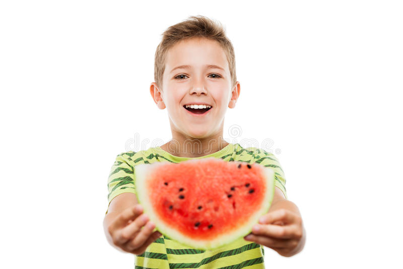 Hübscher lächelnder Kinderjunge, der rote Wassermelonenfruchtscheibe hält stockfoto