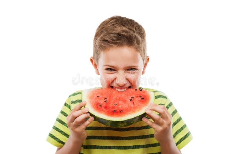 Hübscher lächelnder Kinderjunge, der rote Wassermelonenfruchtscheibe hält stockbild