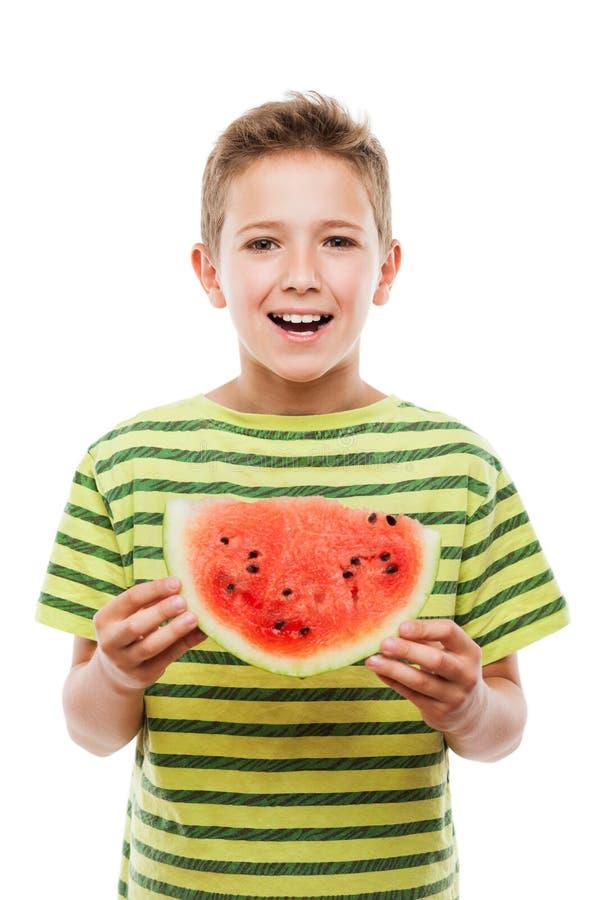 Hübscher lächelnder Kinderjunge, der rote Wassermelonenfruchtscheibe hält lizenzfreie stockbilder