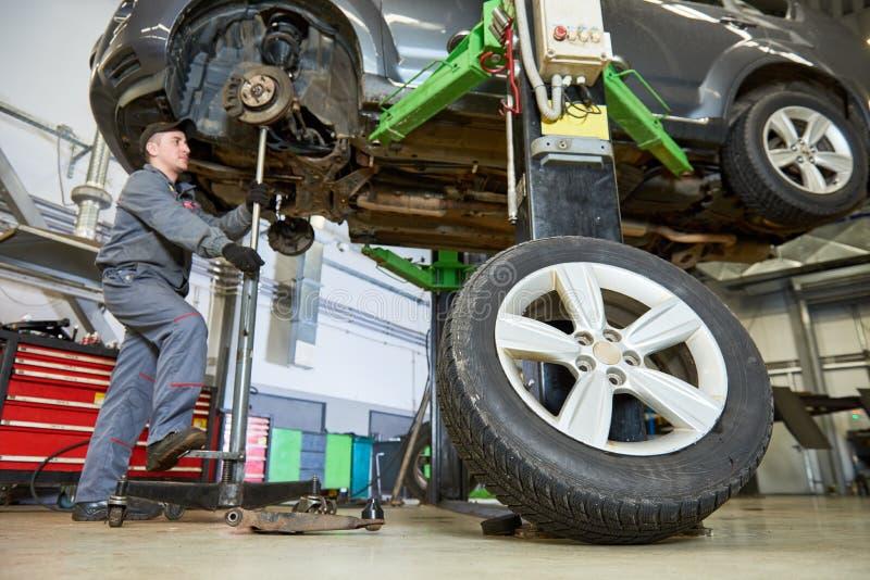 Hübscher lächelnder Mechaniker Mechaniker arbeitet mit Auto lizenzfreies stockbild