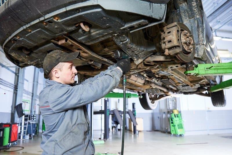 Hübscher lächelnder Mechaniker Mechaniker arbeitet mit Autosuspendierung stockfotografie