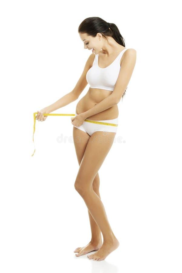 Hübscher lächelnder messender Körper der Frau stockbild