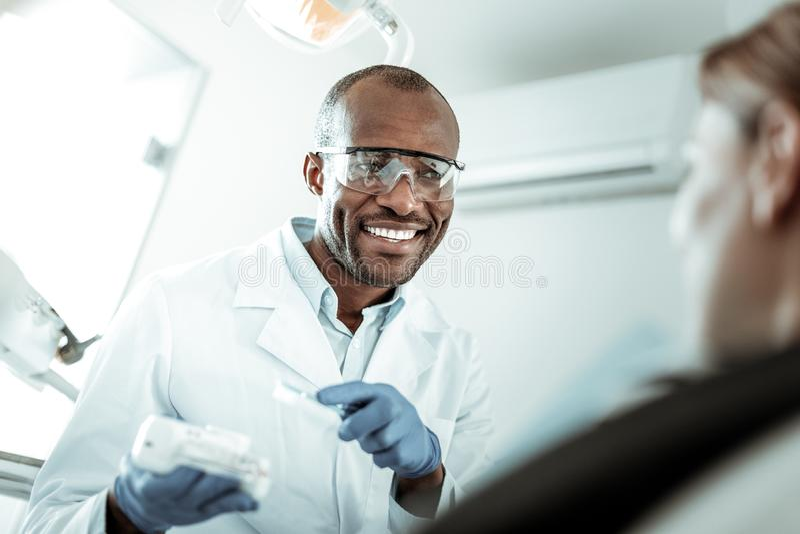 Hübscher lächelnder Zahnarzt, der Aufmerksamkeit auf Kiefermodell betont stockbilder