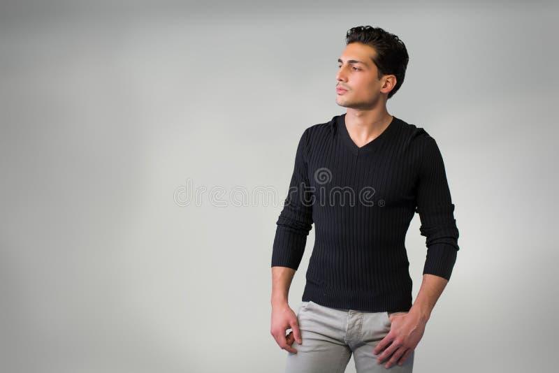 Hübscher lateinischer junger Mann, der auf grauem Hintergrund steht. lizenzfreie stockfotos