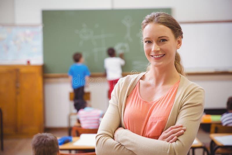 Hübscher Lehrer, der an der Kamera an der Rückseite des Klassenzimmers lächelt lizenzfreie stockfotografie