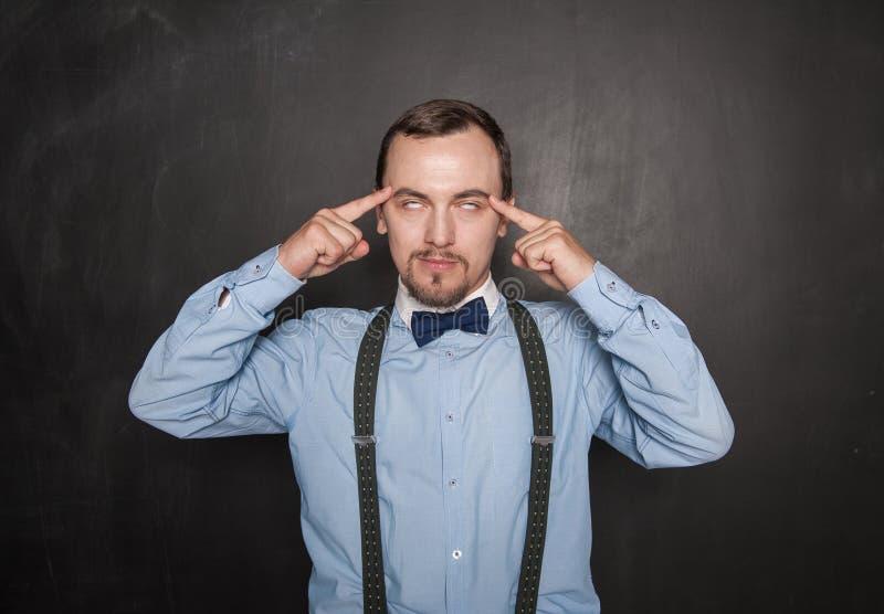 Hübscher Lehrer oder Geschäftsmann, der auf Tafel denkt stockfoto