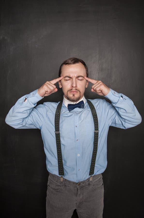 Hübscher Lehrer oder Geschäftsmann, der auf Tafel denkt lizenzfreies stockfoto