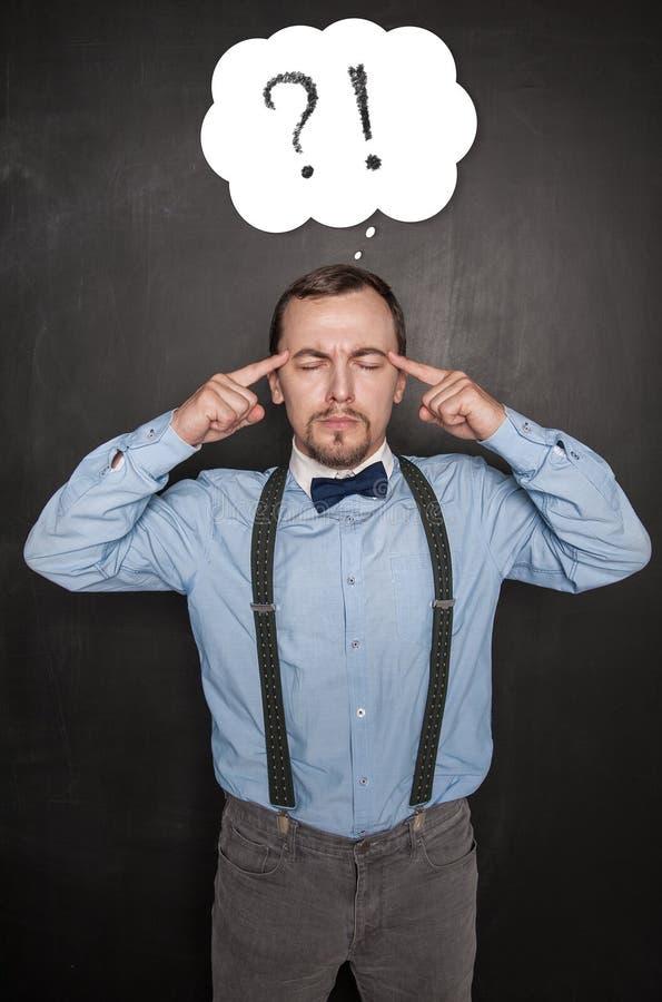 Hübscher Lehrer oder Geschäftsmann, der auf Tafel denkt stockbilder
