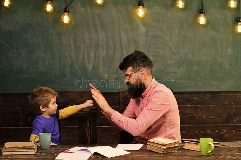 Hübscher Lehrer und nettes Kind, die im Klassenzimmer spielt Schüler, der die Aufgabe erzielt Kleiner Meistergruß stockfotografie