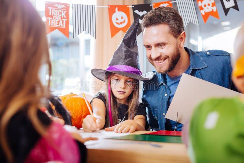 Hübscher liebevoller Vater, der seine Kinder zeichnen Halloween-Bilder verbindet lizenzfreies stockbild