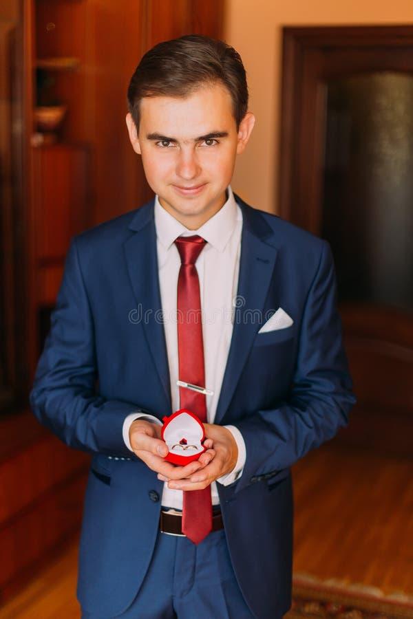 Hübscher Luxus kleidete Mann im stilvollen Blau, das roten Herz-förmigen Kasten mit Eheringen hält Klassischer hölzerner Rauminne lizenzfreie stockfotos