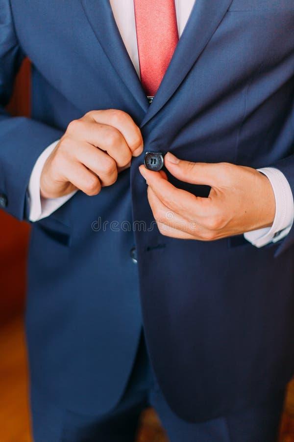 Hübscher Luxus kleidete Mann im stilvollen blauen Anzug mit dem Knöpfen seiner Jacke Cllose-up lizenzfreie stockfotografie