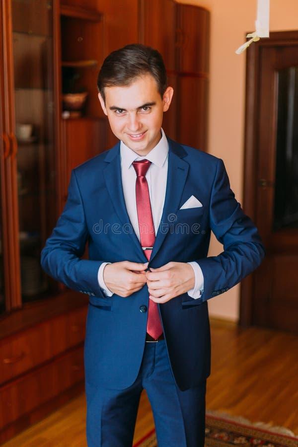 Hübscher Luxus kleidete Mann im stilvollen blauen Anzug mit dem Knöpfen seiner Jacke Klassischer hölzerner Rauminnenraum als Hint stockbild