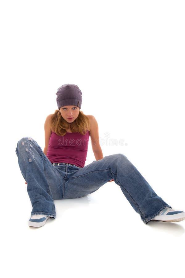 Hübscher Mädchenjugendlicher, der auf weißem Hintergrund sitzt lizenzfreie stockfotografie