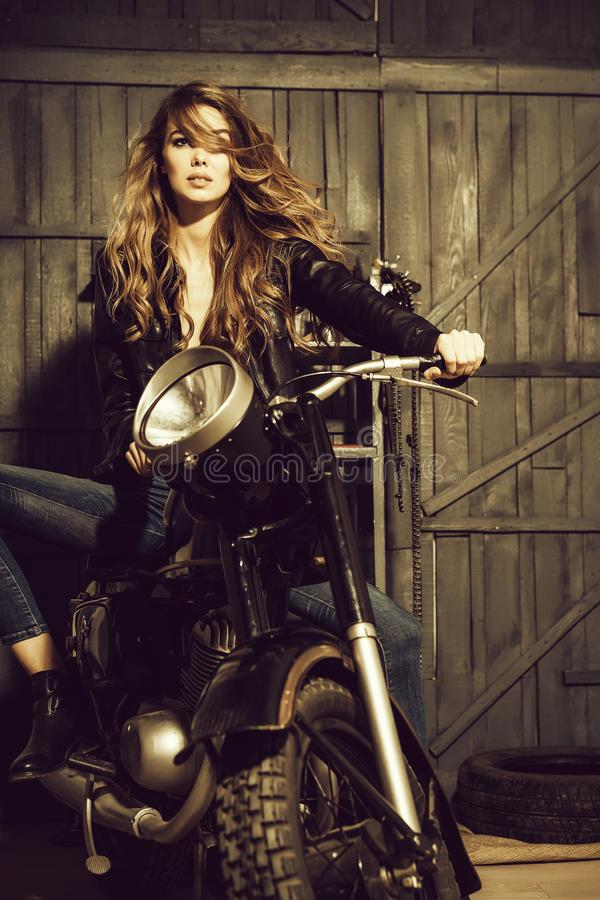 Hübscher Mädchenradfahrer in der Lederjacke, die auf Weinlesemotorrad sitzt lizenzfreies stockbild