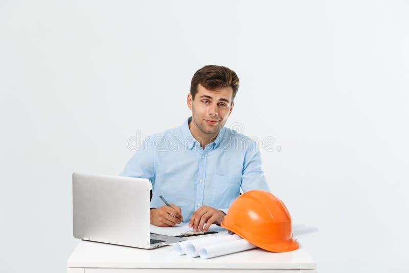 Hübscher männlicher Bauingenieur, der im Büro mit Laptop arbeitet lizenzfreie stockfotografie
